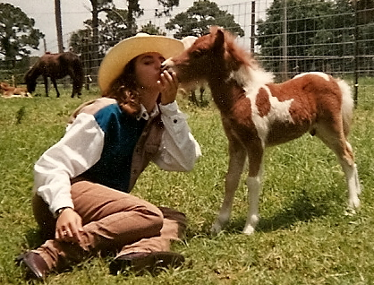 Girl kissing miniature horse foal in 1989